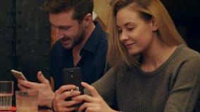 Pares jovenes usando los teléfonos celulares y tomar la foto del selfie del funnie que se sienta en café almacen de metraje de vídeo