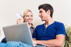 Pares jovenes usando un ordenador portátil y una tarjeta de crédito para las compras en línea fotos de archivo libres de regalías