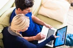 Pares jovenes usando un ordenador portátil y una tarjeta de crédito para las compras en línea imagenes de archivo