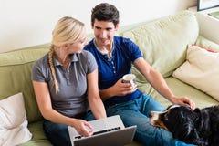Pares jovenes usando un ordenador portátil y una tarjeta de crédito para las compras en línea fotos de archivo
