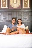 Pares jovenes usando un Tablet PC en una habitación asiática Fotos de archivo libres de regalías