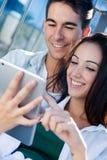Pares jovenes usando una tableta digital Imagenes de archivo