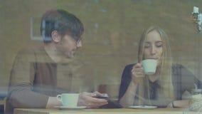 Pares jovenes usando una tableta en el café almacen de metraje de vídeo
