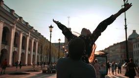 Pares jovenes, varón y hembra, bailando en la calle de la puesta del sol, ellos que dan vuelta y que giran almacen de video
