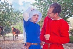 Pares jovenes vestidos como gente medieval Foto de archivo libre de regalías
