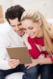 Pares jovenes vivaces que leen su tableta imagenes de archivo