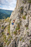 Pares jovenes y adolescente que suben en la roca Fotografía de archivo