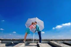Pares jovenes y bonitos que se besan en el tejado debajo del paraguas o foto de archivo libre de regalías