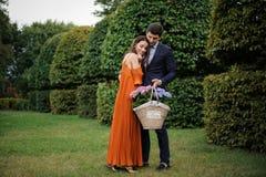 Pares jovenes y elegantes con la cesta de mimbre grande llena de flores Fotografía de archivo