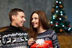 Pares jovenes y felices con los regalos de Navidad Imagen de archivo libre de regalías