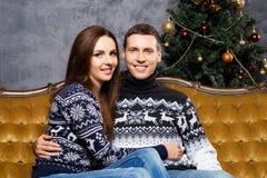 Pares jovenes y felices en un fondo de la Navidad Imagen de archivo libre de regalías