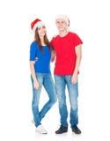 Pares jovenes y felices que presentan en sombreros de la Navidad Fotografía de archivo