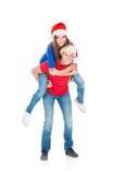 Pares jovenes y felices que presentan en sombreros de la Navidad Imagen de archivo