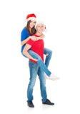 Pares jovenes y felices que presentan en sombreros de la Navidad Imágenes de archivo libres de regalías