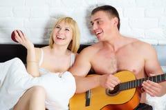 Pares jovenes y hermosos con la guitarra Foto de archivo libre de regalías