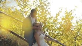 Pares jovenes y hermosos de la boda junto en el parque cerca del río Novio y novia preciosos Día de boda Cámara lenta almacen de metraje de vídeo