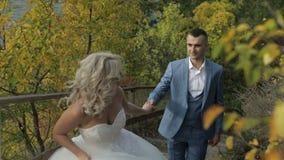 Pares jovenes y hermosos de la boda junto en el parque cerca del río Novio y novia preciosos Día de boda Cámara lenta almacen de video