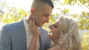 Pares jovenes y hermosos de la boda junto en el parque cerca del río Novio y novia preciosos Día de boda Cámara lenta metrajes