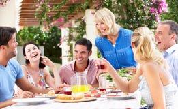 Pares jovenes y mayores que disfrutan de la comida de la familia Fotografía de archivo