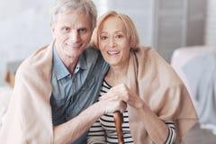 Pares jubilados adorables que abrazan y que sonríen en cámara imagenes de archivo