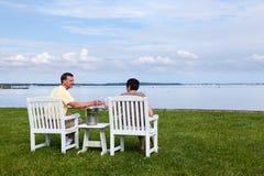 Pares jubilados casados por la bahía con champán Fotos de archivo