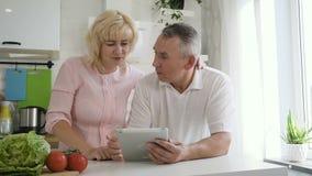 Pares jubilados caucásicos que hacen compras en línea usando la tableta almacen de video