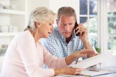 Pares jubilados con las cuentas del hogar Imagen de archivo libre de regalías