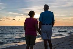 Pares jubilados que llevan a cabo las manos en la playa imagenes de archivo