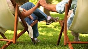 Pares jubilados que se sientan en las sillas de cubierta que llevan a cabo las manos almacen de metraje de vídeo