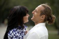 Pares juguetones del amor que sonríen en parque del verano Imagenes de archivo
