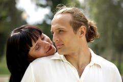 Pares juguetones del amor que sonríen en parque del verano Imagen de archivo