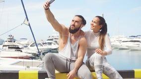 Pares juguetones el las vacaciones de verano de la playa, tomando la foto del selfie almacen de metraje de vídeo