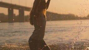 Pares juguetones en el amor que juega con agua en el río en puesta del sol almacen de metraje de vídeo