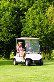 Pares juguetones jovenes con el carro de golf en un curso Imagen de archivo libre de regalías