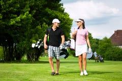 Pares juguetones jovenes que juegan a golf en un curso Foto de archivo