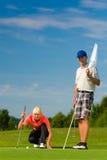 Pares juguetones jovenes que juegan a golf en un curso Foto de archivo libre de regalías
