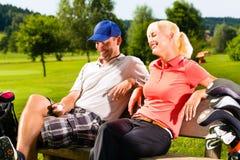 Pares juguetones jovenes que juegan a golf en un curso Imágenes de archivo libres de regalías