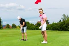 Pares juguetones jovenes que juegan a golf en un curso Imagen de archivo