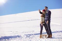 Pares juguetones jovenes que se divierten sledging abajo de la colina nevada Fotografía de archivo libre de regalías