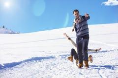 Pares juguetones jovenes que se divierten sledging abajo de la colina nevada Foto de archivo
