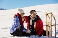 Pares juguetones jovenes que se divierten sledging abajo de la colina nevada Imagenes de archivo