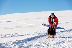 Pares juguetones jovenes que se divierten sledging abajo de la colina nevada Imagen de archivo libre de regalías