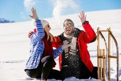 Pares juguetones jovenes que se divierten sledging abajo de la colina nevada Imágenes de archivo libres de regalías