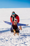 Pares juguetones jovenes que se divierten sledging abajo de la colina nevada Imagen de archivo