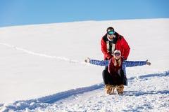 Pares juguetones jovenes que se divierten sledging abajo de la colina nevada Fotografía de archivo