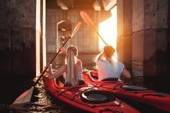 Pares kayaking en puesta del sol Fotos de archivo