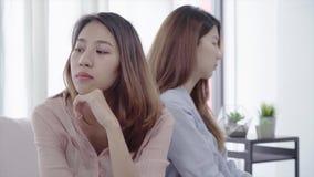 Pares lésbicas asiáticos infelizes do lgbt que sentam cada lado do sofá com emoção temperamental na sala de visitas video estoque