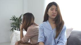 Pares lésbicas asiáticos infelizes do lgbt que sentam cada lado do sofá com emoção temperamental na sala de visitas filme