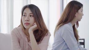 Pares lésbicas asiáticos infelizes do lgbt que sentam cada lado do sofá com emoção temperamental na sala de visitas vídeos de arquivo