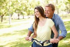 Pares latino-americanos ao ar livre no parque com bicicleta Fotos de Stock Royalty Free